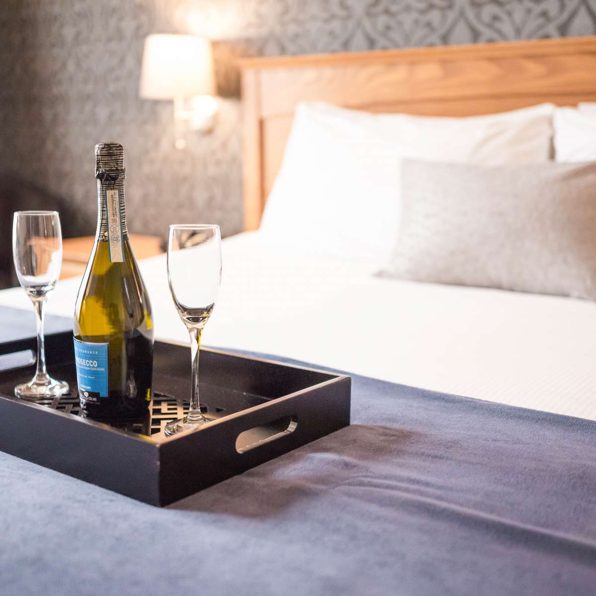 King sized bed with serving tray containing two glasses and a bottle of champagne